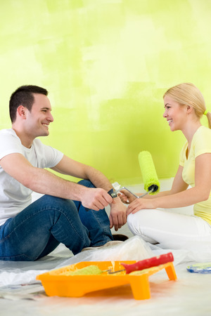 Affectionate couple sitting on floor after painting  photo