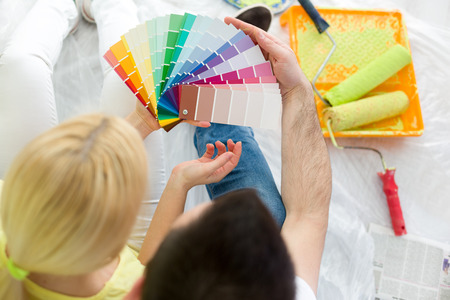 paint samples:  Top view of couple choosing colors to paint new house