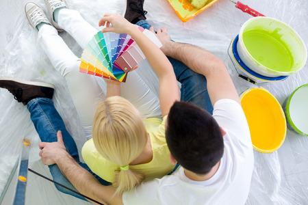 塗装色のサンプルを見て、新しい家を描画する色を選択するカップル 写真素材
