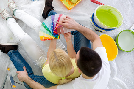 Couple sitting on floor surrounded equipment for painting and chooses a color, top view