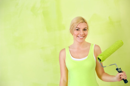 Portrait of smiling woman  as painter worker with paint roller photo