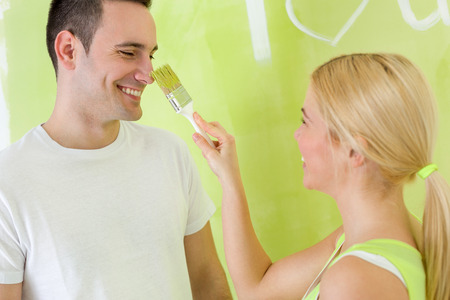 Loving couple having fun at home renovation, painting photo