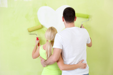Couple painting new home together, back view  photo