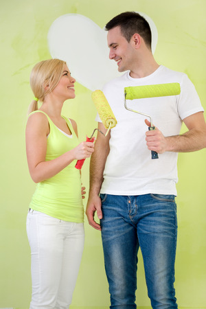 Young affectionate couple with paint rollers looking at each other photo