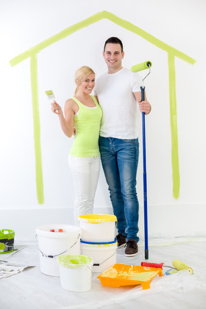 painting and decorating:  Happy couple painting their new home with panted home on wall in background  Stock Photo