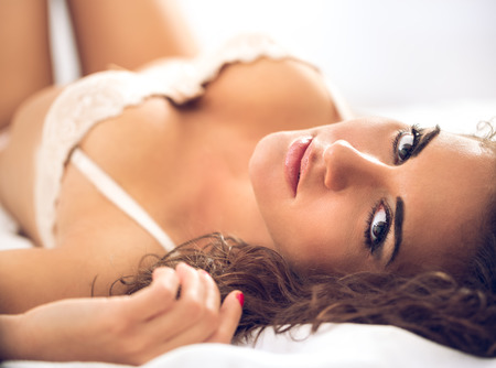 sexual woman relaxing and lying in bed wearing elegant bra, looking at camera