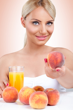Young healthy woman with natural peach juice photo
