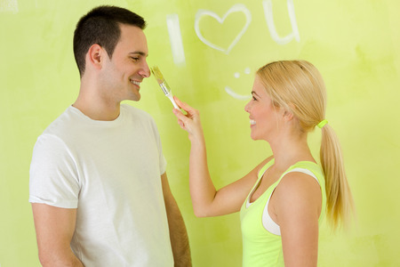 couple playing with paint brush,  young girl painting nose her boyfriend photo