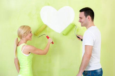 Love young couple painting heart on wall photo