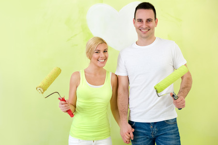 Portrait of smiling couple in love with paint rollers photo