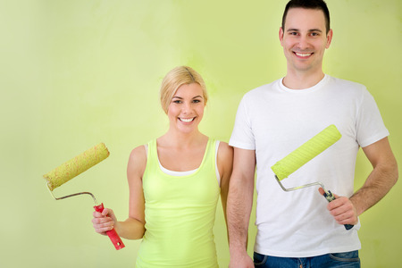 Young lovers couple, smiling and holding equipment for painting photo