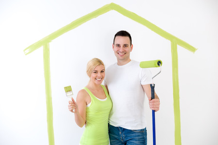 Portrait of smiling, young couple ready to painting their home photo