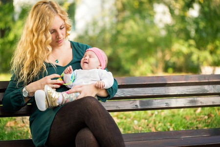 Mom soothes a crying baby, sitting on a park bench photo