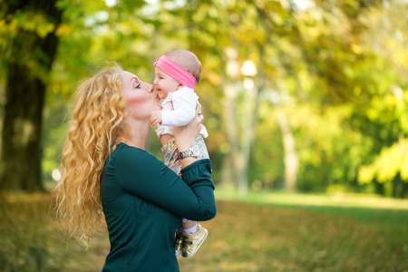 Happy cheerful family, mother and baby kissing in nature outdoor photo