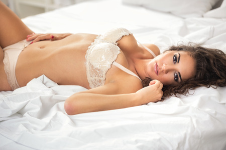 sexual girl lie on white sheet in underwear photo