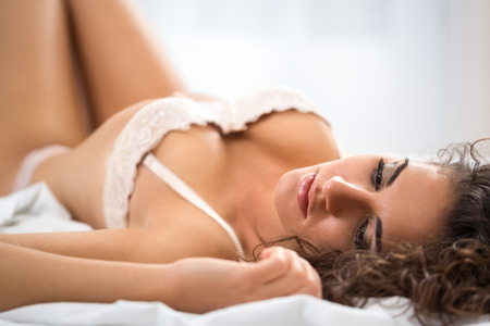 Woman in ecstasy lying in underwear on bed photo