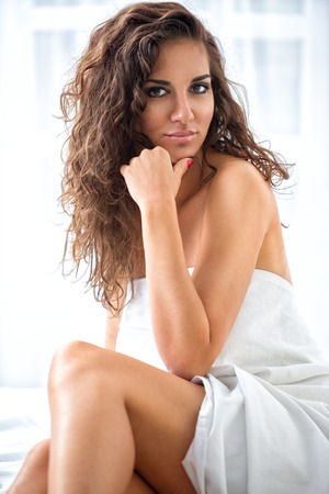 Seductive woman wrapped in a sheet in a bedroom photo