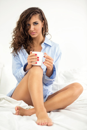 Sexy young woman with coffee in morning  photo
