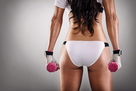 sexy ass of sportswoman with dumbbells, back view photo