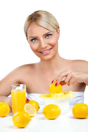 Beautiful woman squeeze on juicer and making lemonade photo