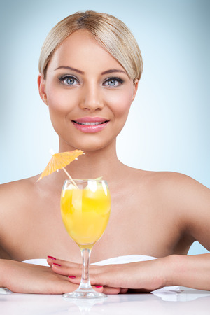 young beautiful blonde woman drinking cocktail in a summertime photo