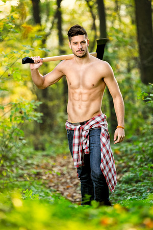 Male babe handsome lumberjack with axe  in forest