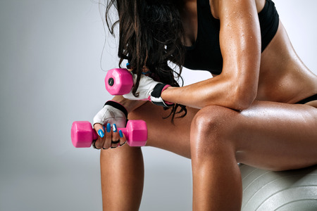 dumbbells:  Sweaty female body after exercise sitting on fitness ball  Stock Photo