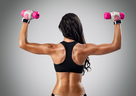 back and hands of a young sporty muscular woman working out with two dumbbells Stock Photo - 28444883