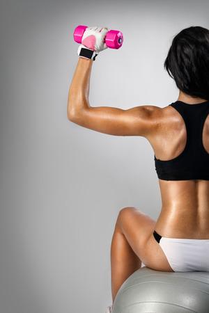 haciendo ejercicio: Fitness mujer haciendo ejercicio con pesas en bola, vista posterior Foto de archivo