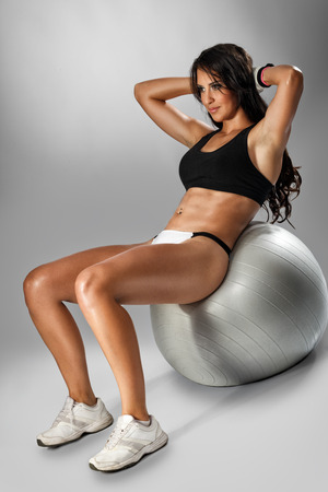 Attractive young woman  doing  abdominal push-ups on fit-ball Stock Photo - 28444887