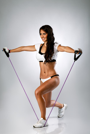Attractive strong woman exercise with  rubber resistance band Stock Photo - 28444888