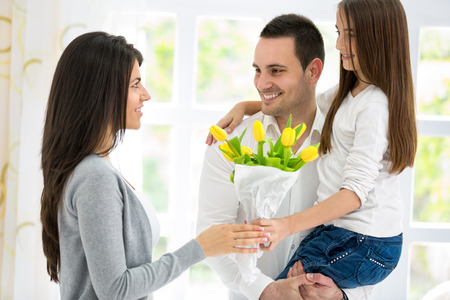 Happy family on mother's Day, father and daughter with flowers