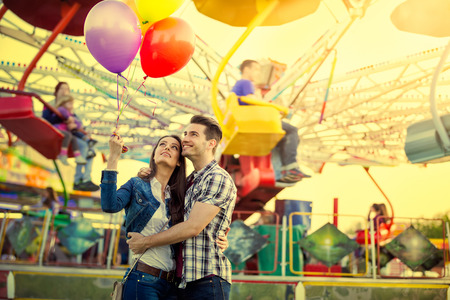 Young couple hugging and holding each other in amusement park while looking at balloons