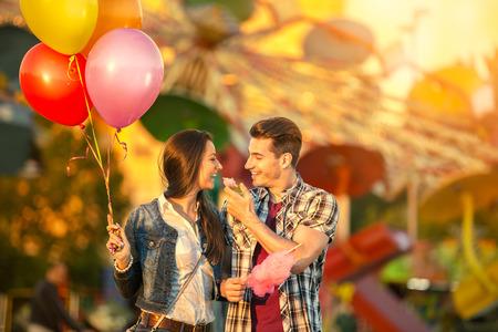 algodon de azucar: Feliz pareja joven comiendo algodón de azúcar en el parque de atracciones Foto de archivo