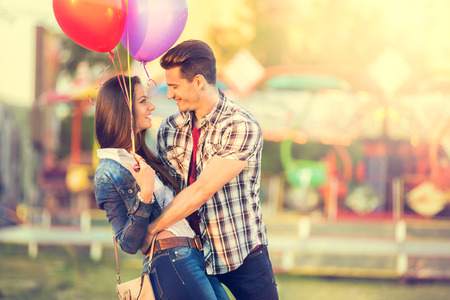 lovers park:  romantic couple in embrace looking at each other with a carousel in the background Stock Photo