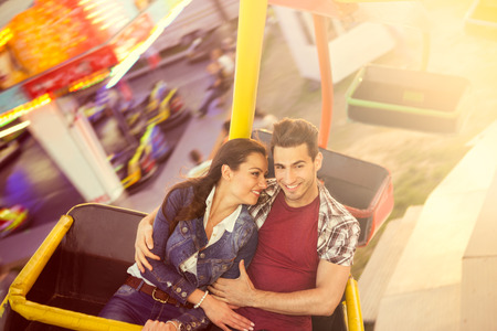 amusement park ride:  Young smilinf couple having a ride on a ferris wheel Stock Photo