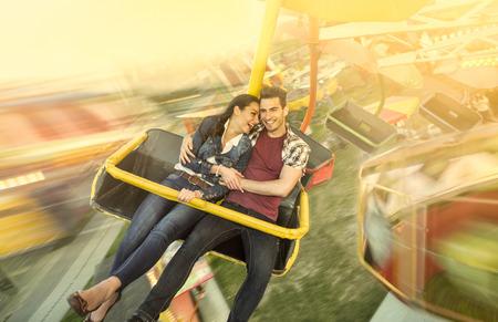 amusement park ride: Happiness couple riding on ferris wheel at amusement park