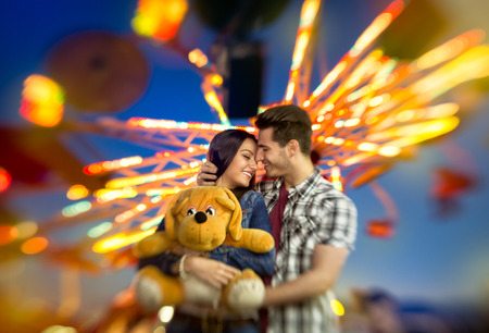 laughing couple:  Love couple with colorful carousel in motion with sundown in background, amusement park ride