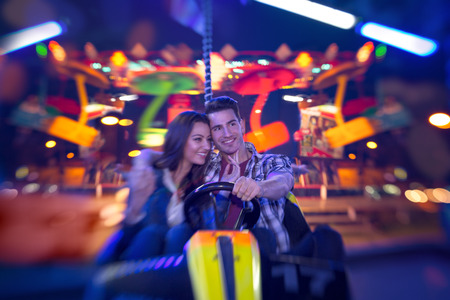 amusement park ride: couple in bumper car playing an attractions park - shoot with lensbaby Stock Photo