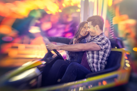 Happy couple ride bumper car on a fun fair amusement Stock Photo