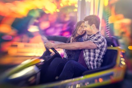 fair woman:  Happy couple ride bumper car on a fun fair amusement Stock Photo