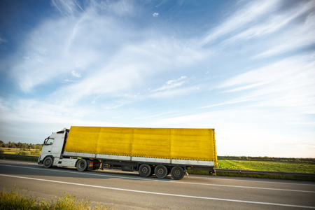 yellow trucks on a road, truck with white head photo