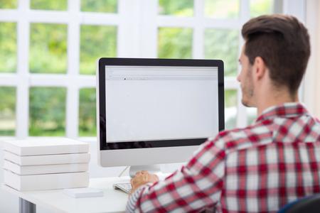 looking at computer screen:  Young man looking at computer screen