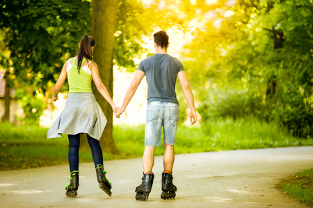 roller skating: couple ride roller skates in the park, back view  Stock Photo