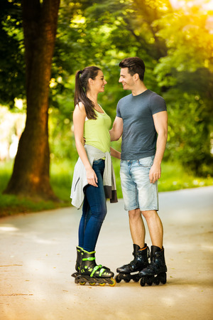Affectionate couple on roller skates,  stand and looking at each other photo
