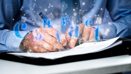 Businessman  at office desk signing a Business contract  photo