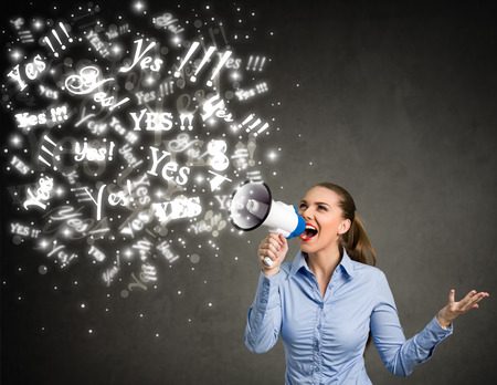 human voice: Young woman screaming yes into a megaphone Stock Photo