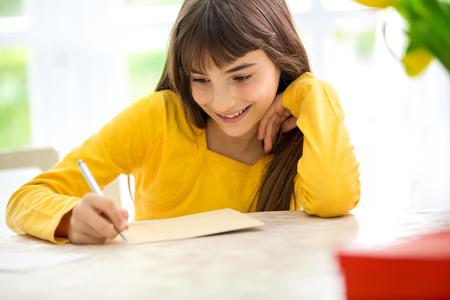 Leuk glimlachend meisje schrijft brief vergadering bureau Stockfoto