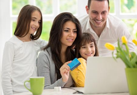 ni�os de compras: Compras de la familia en l�nea, dos gemelos ni�as ingenio padre y su madre que gozan en las compras Foto de archivo
