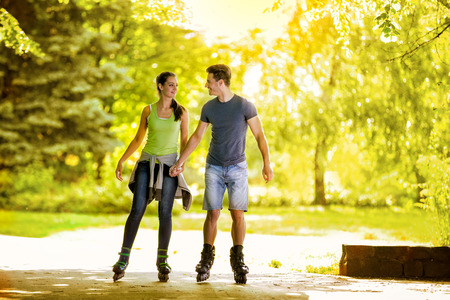 roller skating:  Young couple holding hands and roller-skating in the park Stock Photo